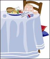 Nino pequeno sentado a la mesa, con comida en el plato