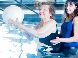 Mayor y cuidadora en la piscina cubierta de la residencia de mayores Sanitas Les Corts